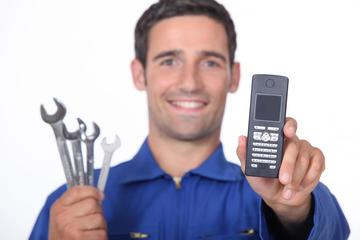 This is a picture of a man holding a phone and tools.
